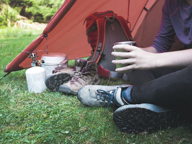 Wanderer sitzt im Zelt und trinkt Kaffee