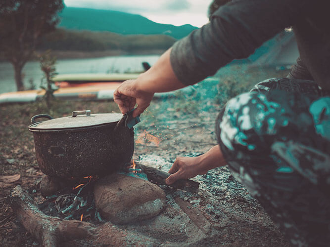 Kochen über dem offenem Lagerfeuer am Wasser