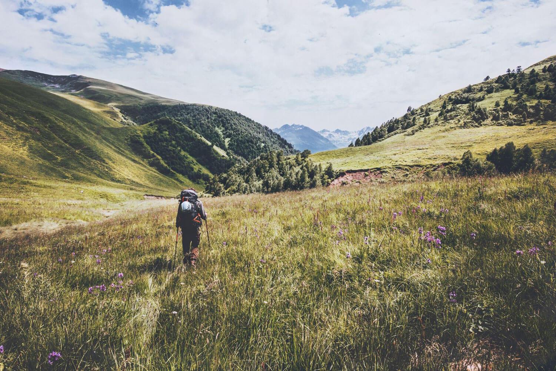 Wanderer mit Trekkinggepäck auf einer Wiese