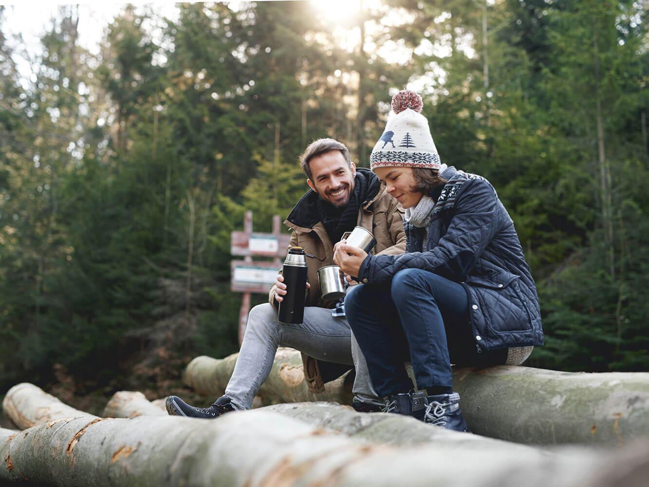 Vater und Sohn im Wald beim Teetrinken