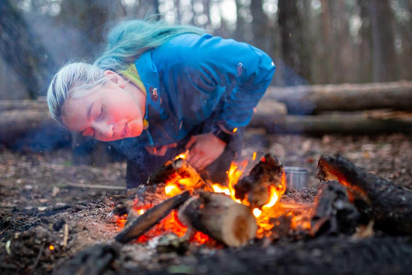 Frau entfacht Feuer beim Wildniskurs