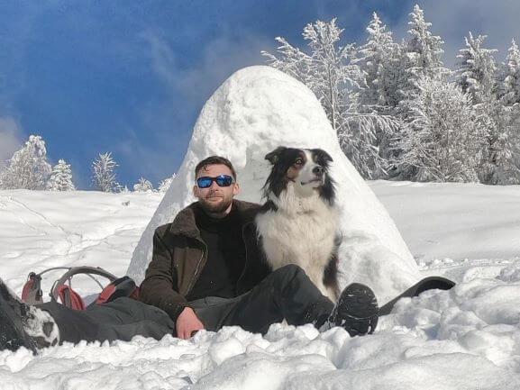 Outdoorguide Julian beim Wintertrekking mit Schulhund Rumo vorm Iglu