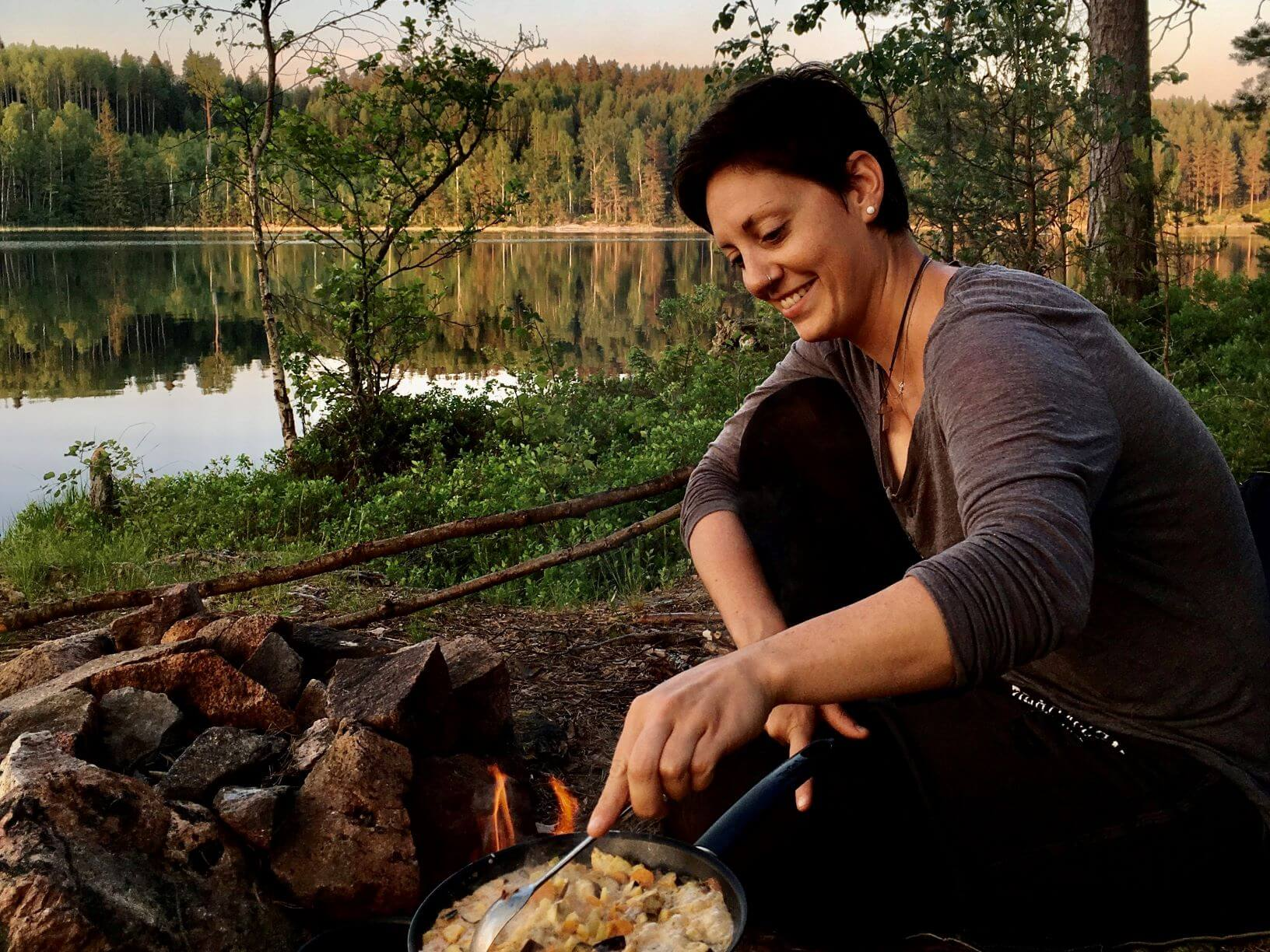 Outdoorguide Lea Wunderli beim Kochen am Lagerfeuer